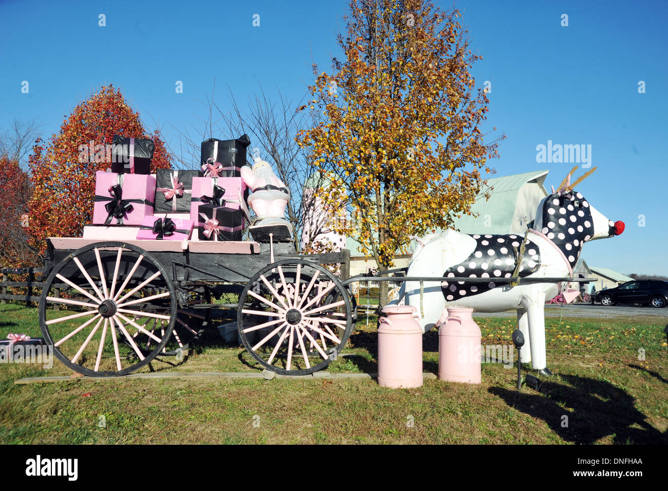 Artsy wagon with gifts and polk-a-dot cow with milk cans Virginia, Polk-a-dot cow, cow, gifts, wagon, farm wagon, milk cans, - Stock Image