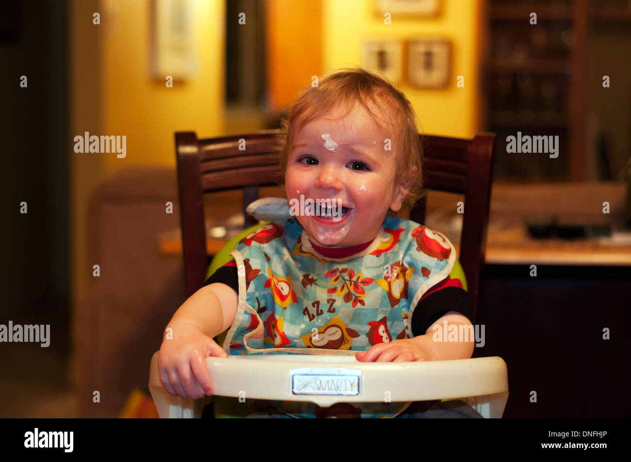 A laughing baby boy with yoghurt on his face - Stock Image