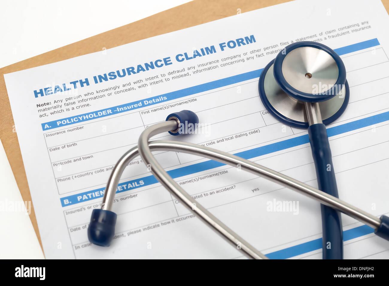 Medical reimbursement with health insurance claim form and stethoscope - Stock Image