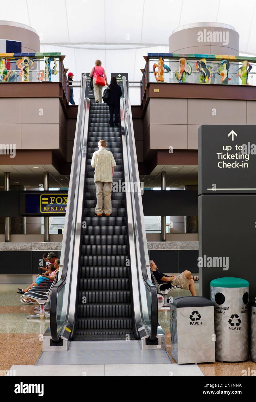 Travelers on escalator, Denver International Airport - Stock Image