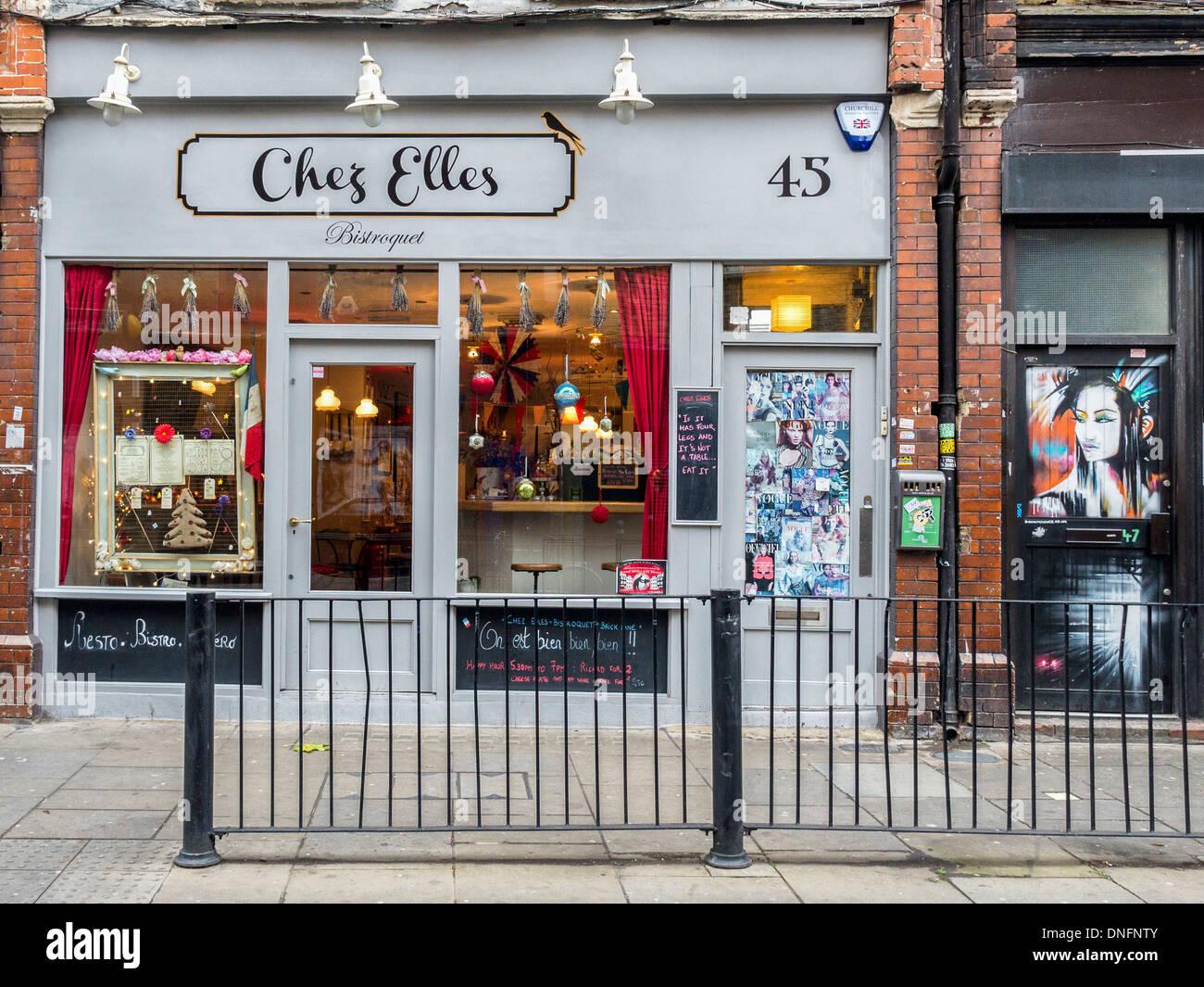 Chez Alles bistroquet bistro and door with street art woman in Brick Lane, London E1 - Stock Image