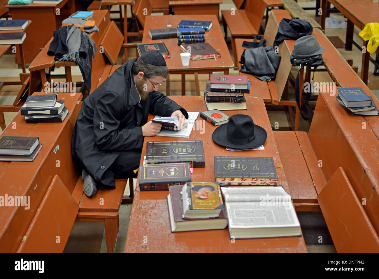 An Orthodox Jewish student studying alone in a large cluttered room at Lubavitch Headquarters in Crown Heights, Brooklyn, NY - Stock Image