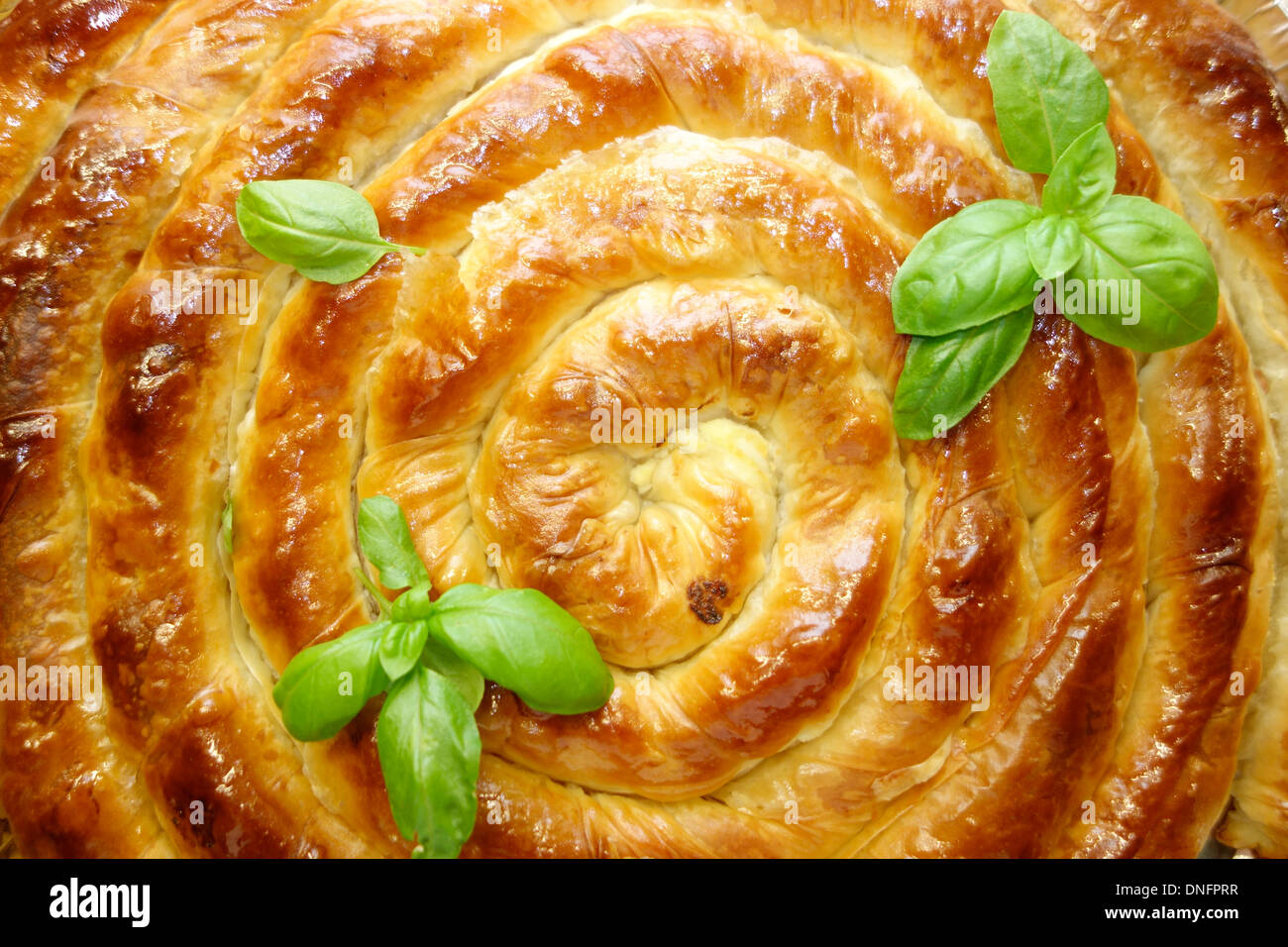 Traditional swirl shaped Balkan pie garnished with fresh basil. - Stock Image