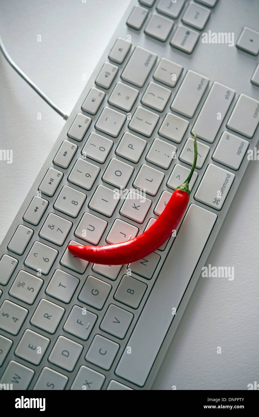 Red hot pepper on a computer keyboard - Stock Image