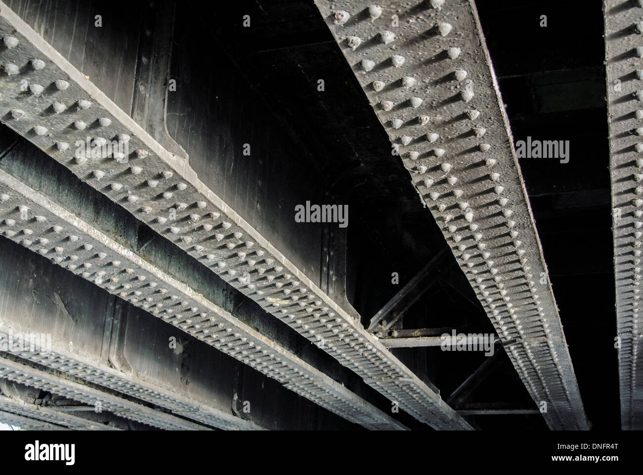 Metal rivets and girders on underside of bridge Stock Photo
