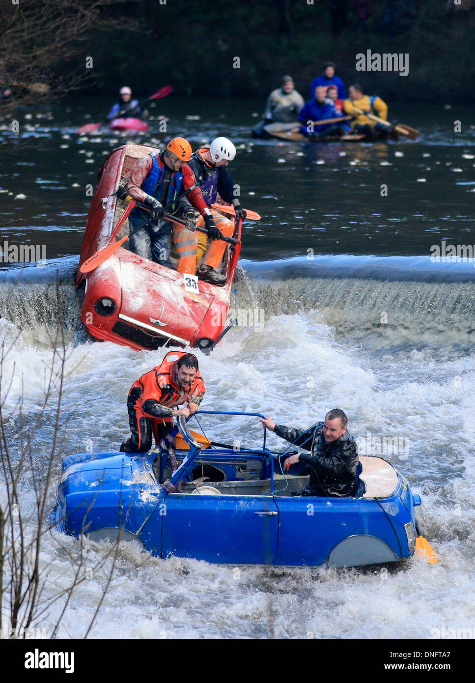 Matlock, Derbyshire, Peak District, UK . 26th Dec, 2013. Competitors take the plunge down a weir on The River Derwent as they take part in the Boxing Day Raft Race at Matlock in the Derbyshire Peak District. Credit:  Joanne Roberts/Alamy Live News - Stock Image