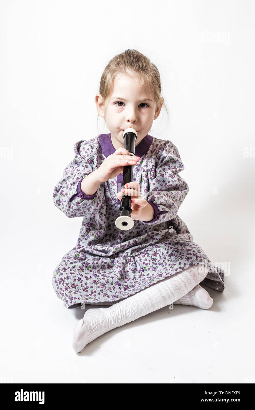 Little cute girl playing the flute on a white background - Stock Image