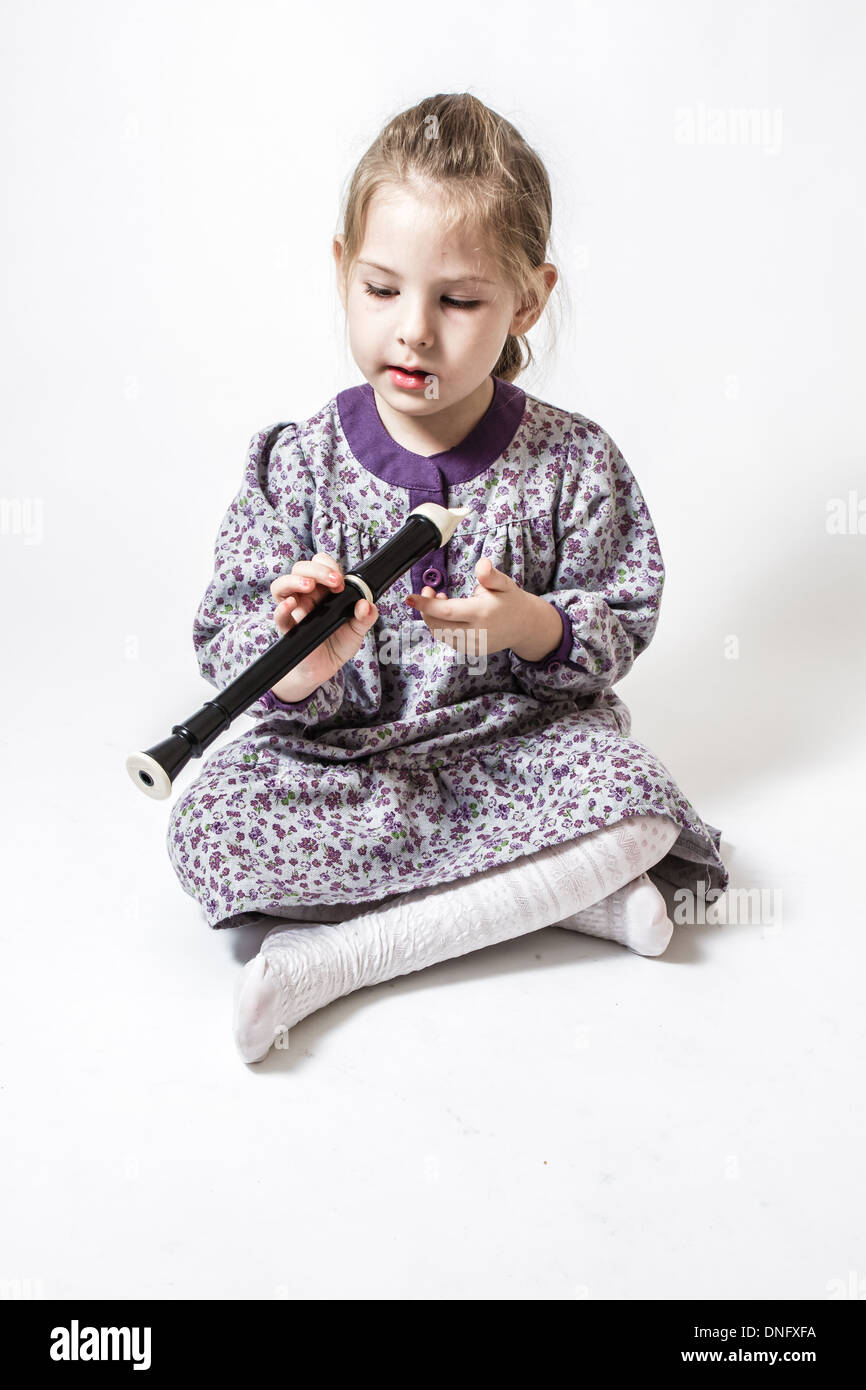 Little cute girl holding the flute on a white background - Stock Image