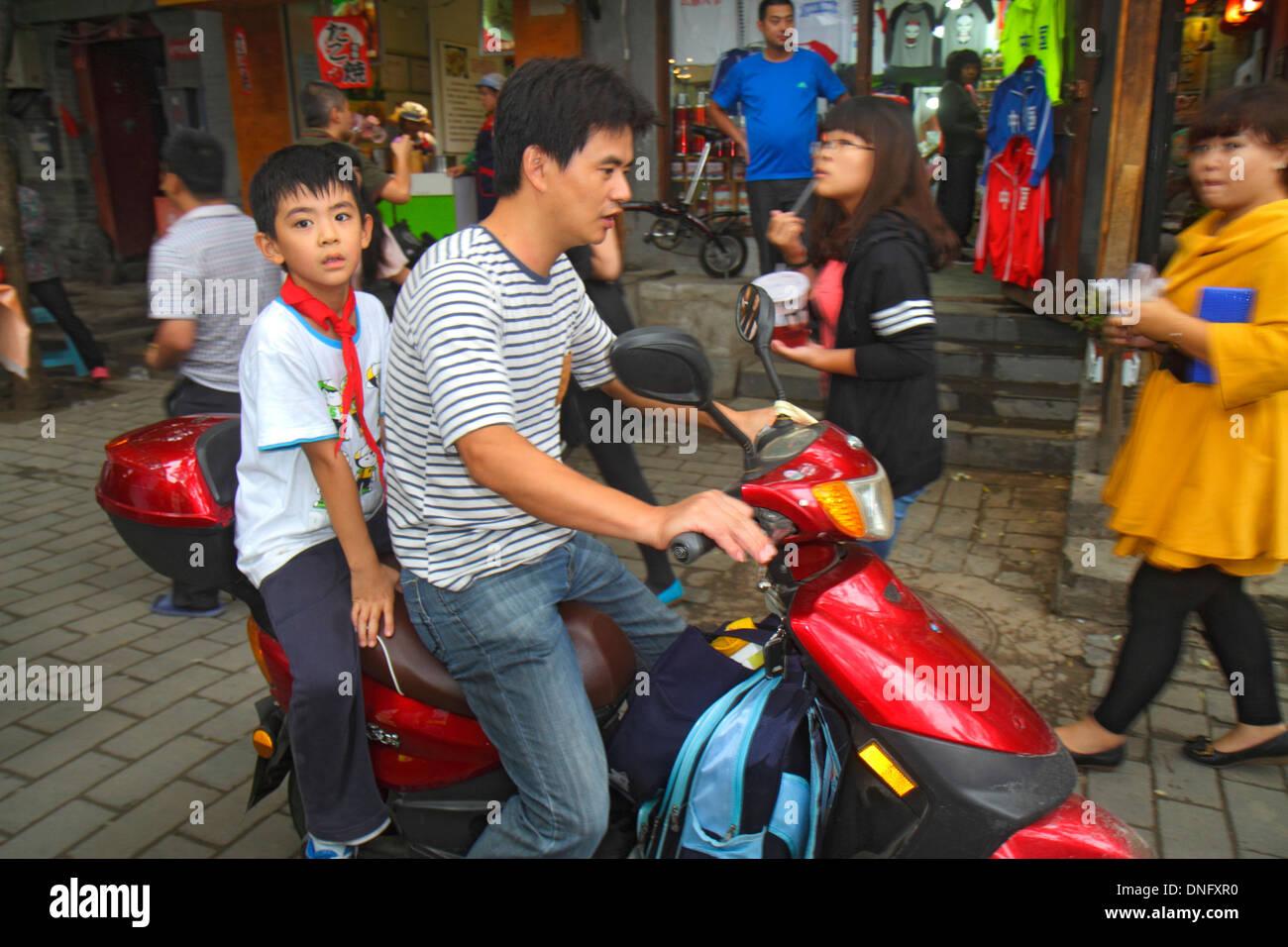 Beijing China Dongcheng District Nanluoguxiang hutong historic shopping Asian man father boy son electric motor scooter no helme - Stock Image