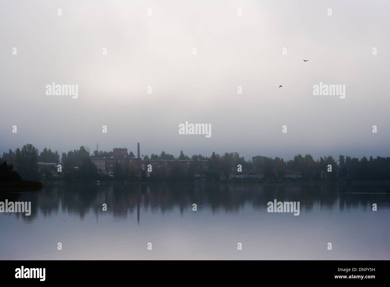 Small town behind a lake on misty overcast morning - Stock Image
