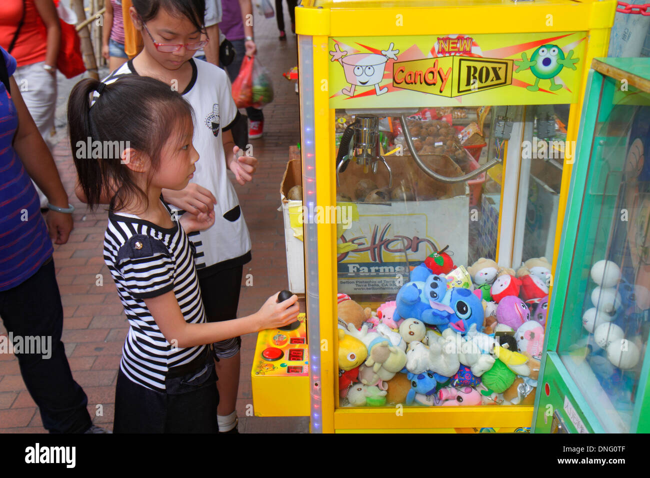 Hong Kong China Kowloon Sham Shui Po Asian girl playing carnival game claw prize stuffed animal - Stock Image