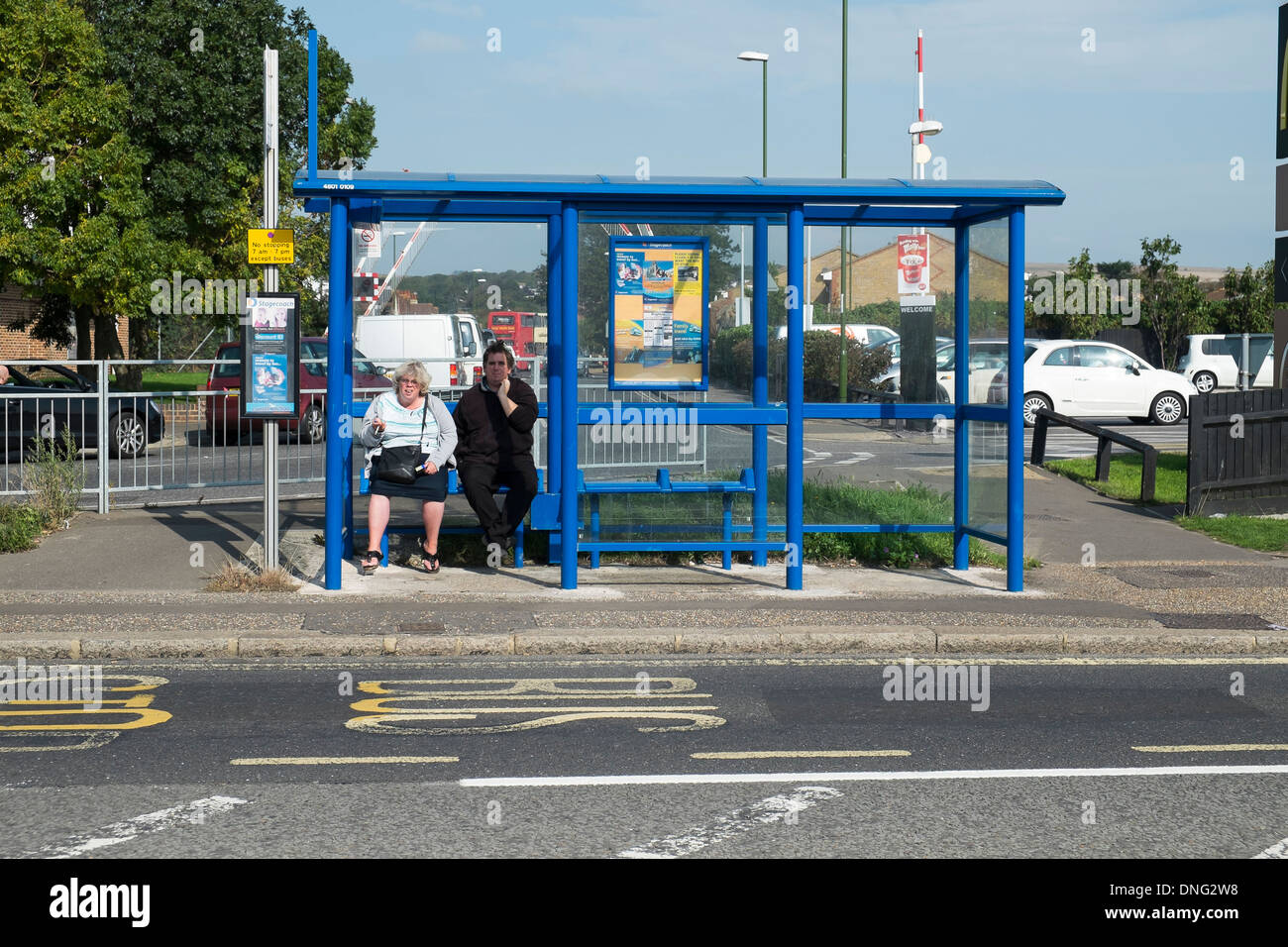 2 persons waiting in a bus stop - Stock Image