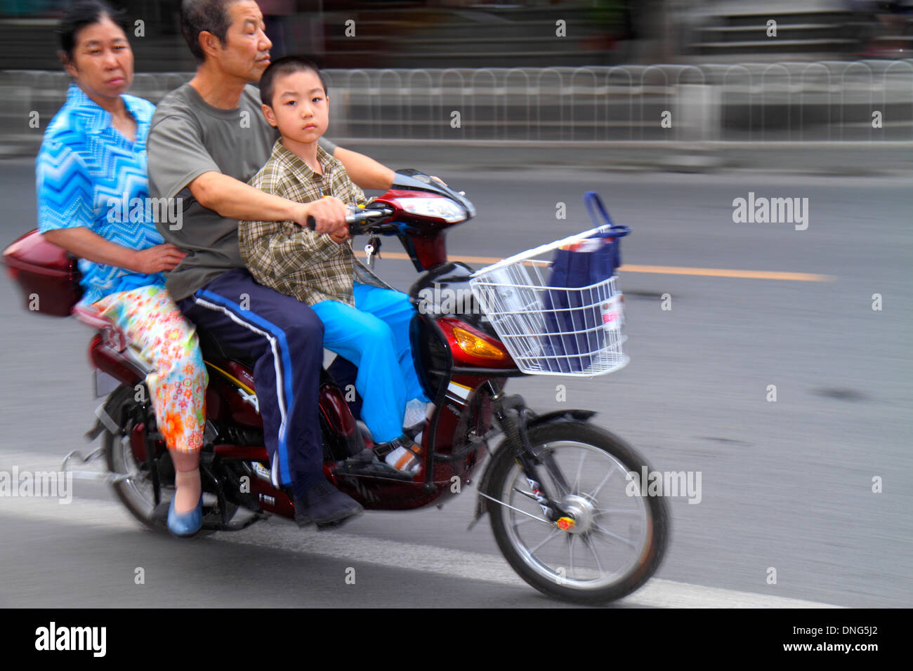 Beijing China Dongcheng District street traffic Asian man woman boy father mother son family no helmet electric bicycle moped pa - Stock Image