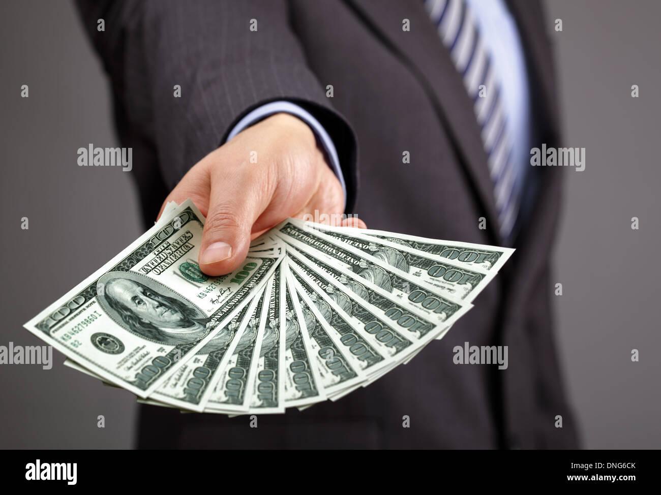 Holding one hundred dollar bills - Stock Image