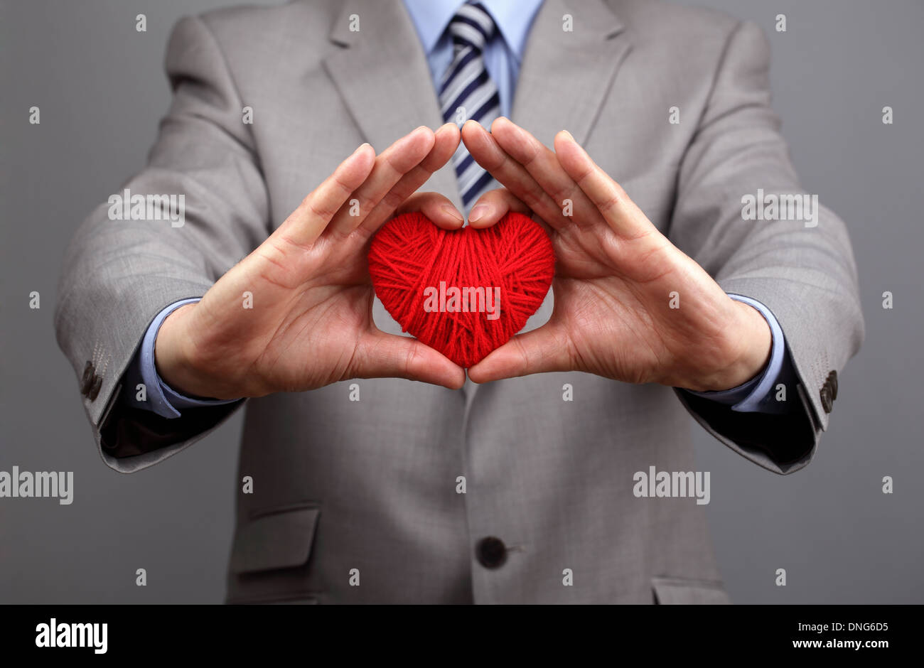 Businessmen is holding out a red heart - Stock Image