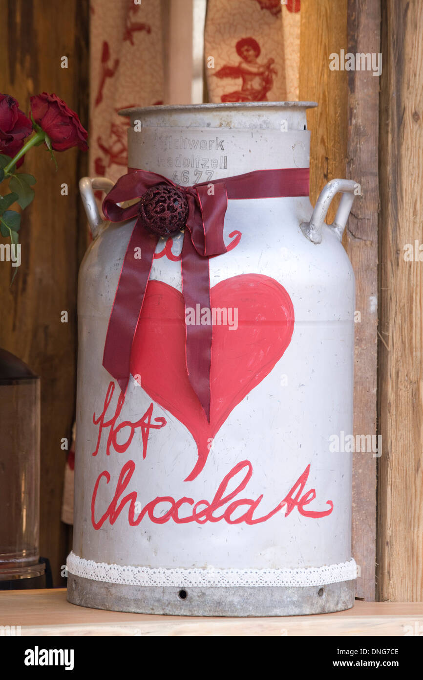 White Milk Churn with a Red Heart and ribbon with the words Hot Chocolate on it - Stock Image