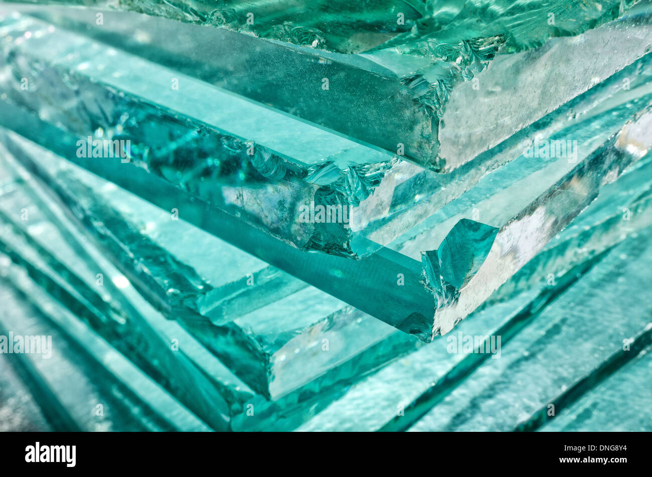 Sharp dangerous edge of plate glass internal reflection brings out green color and depth - Stock Image