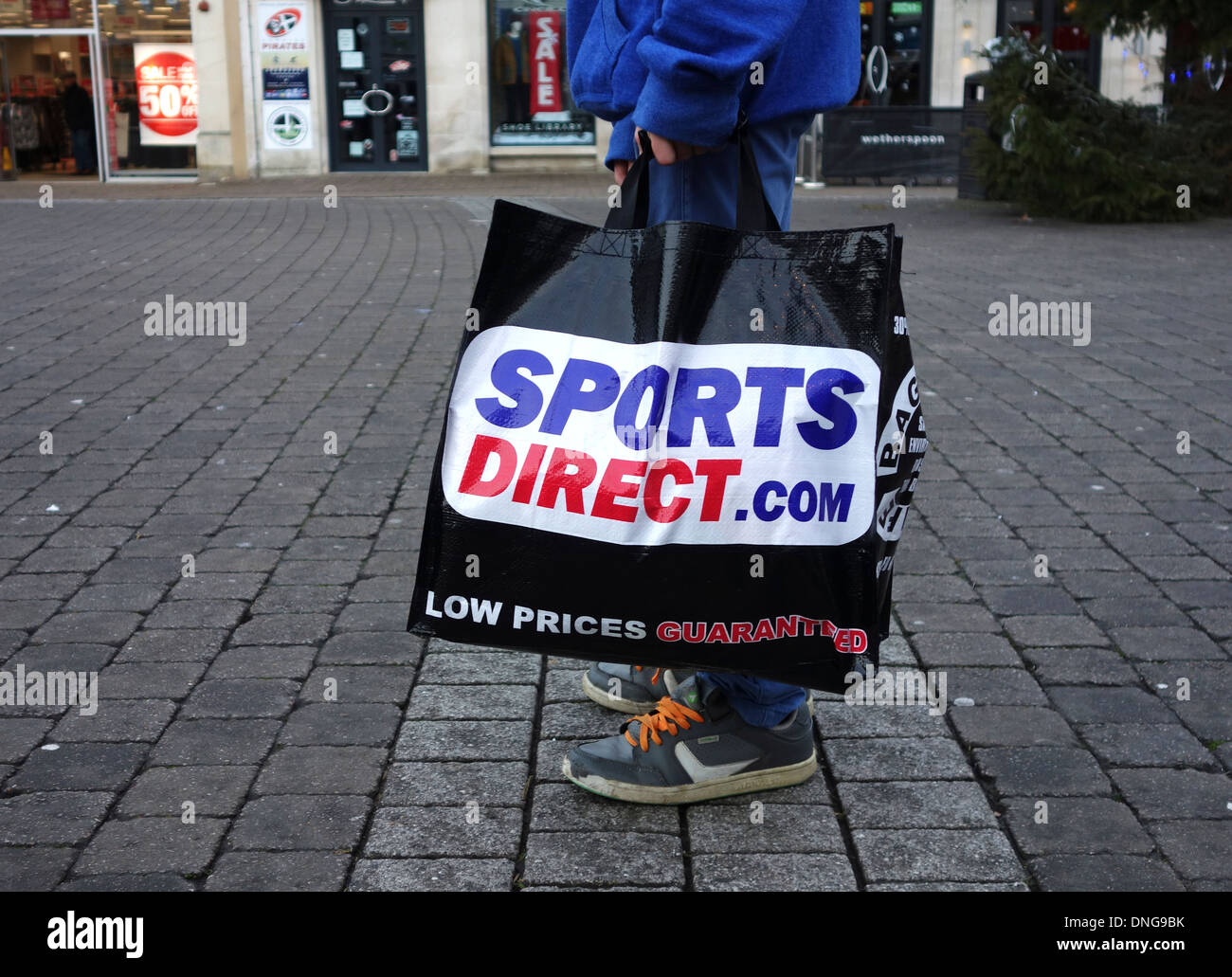 a customer carrying a sports direct shopping bag - Stock Image