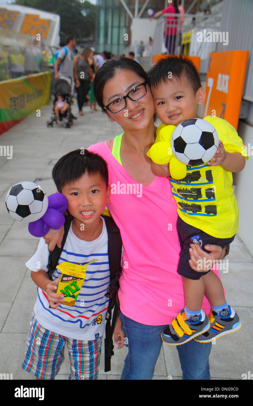 Hong Kong China Kowloon Prince Edward Mong Kok Stadium Sun Pegasus football club soccer fans Asian woman mother boy son brothers - Stock Image