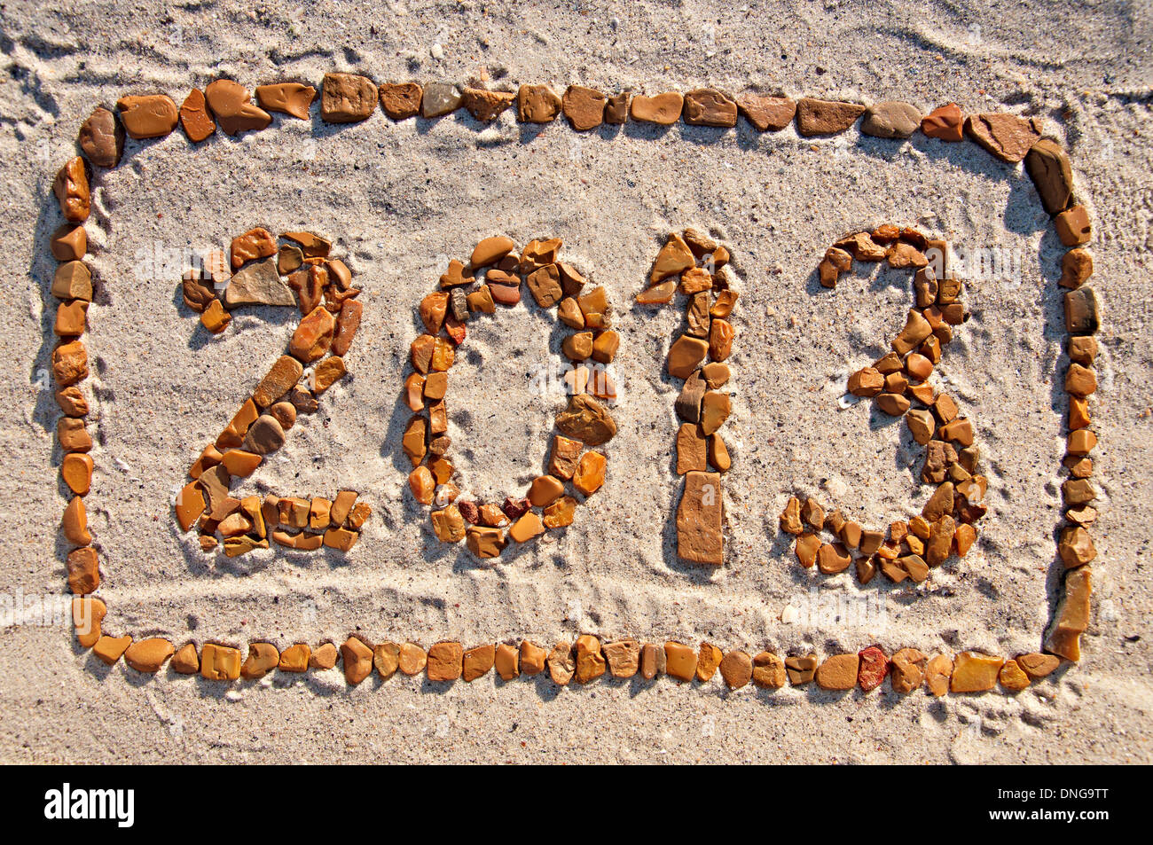 Digits 2013 - numbers in the frame, lined with pebbles on the sand. - Stock Image