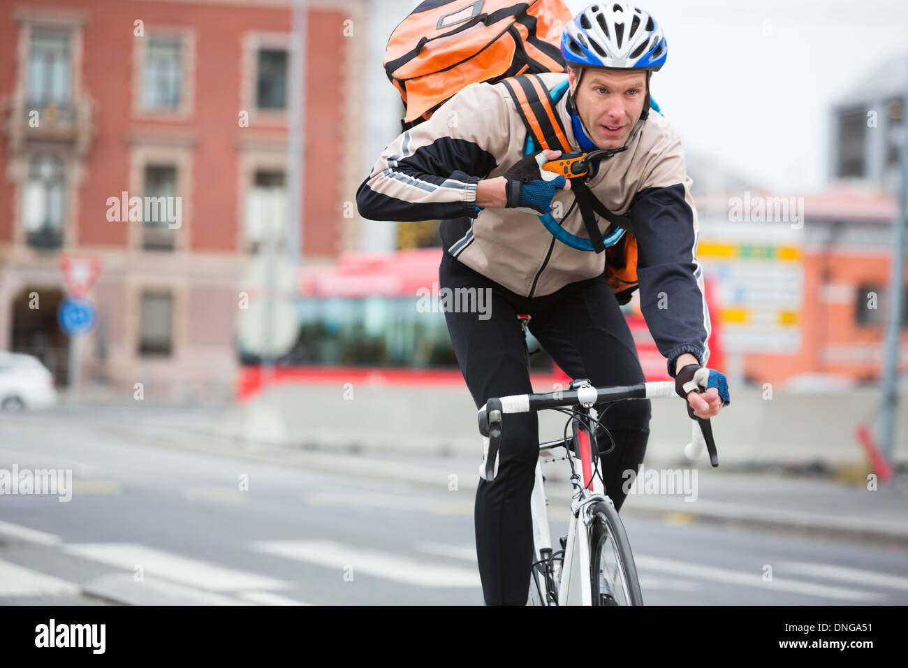 Male Cyclist With Courier Delivery Bag Riding Bicycle - Stock Image