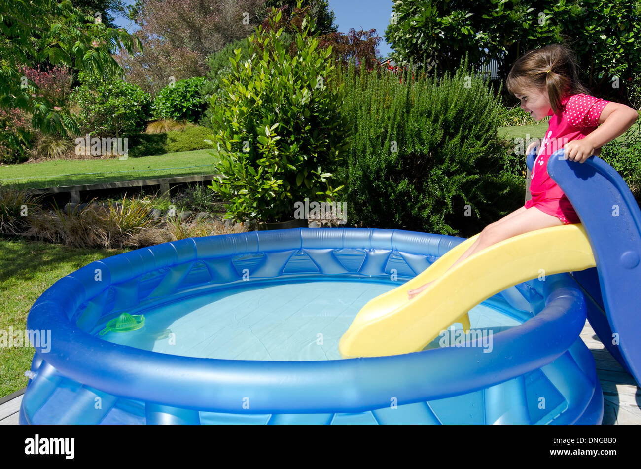 child girl slides on a slide into cool waters in a children stock