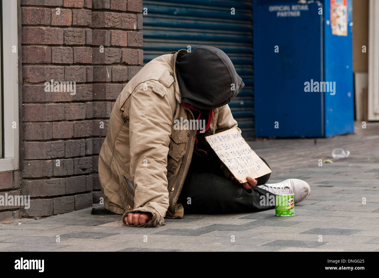 Homeless man begging on Sauchihall Street in Glasgow, Scotland, UK. He is sitting next to a shop that has been closed down. - Stock Image