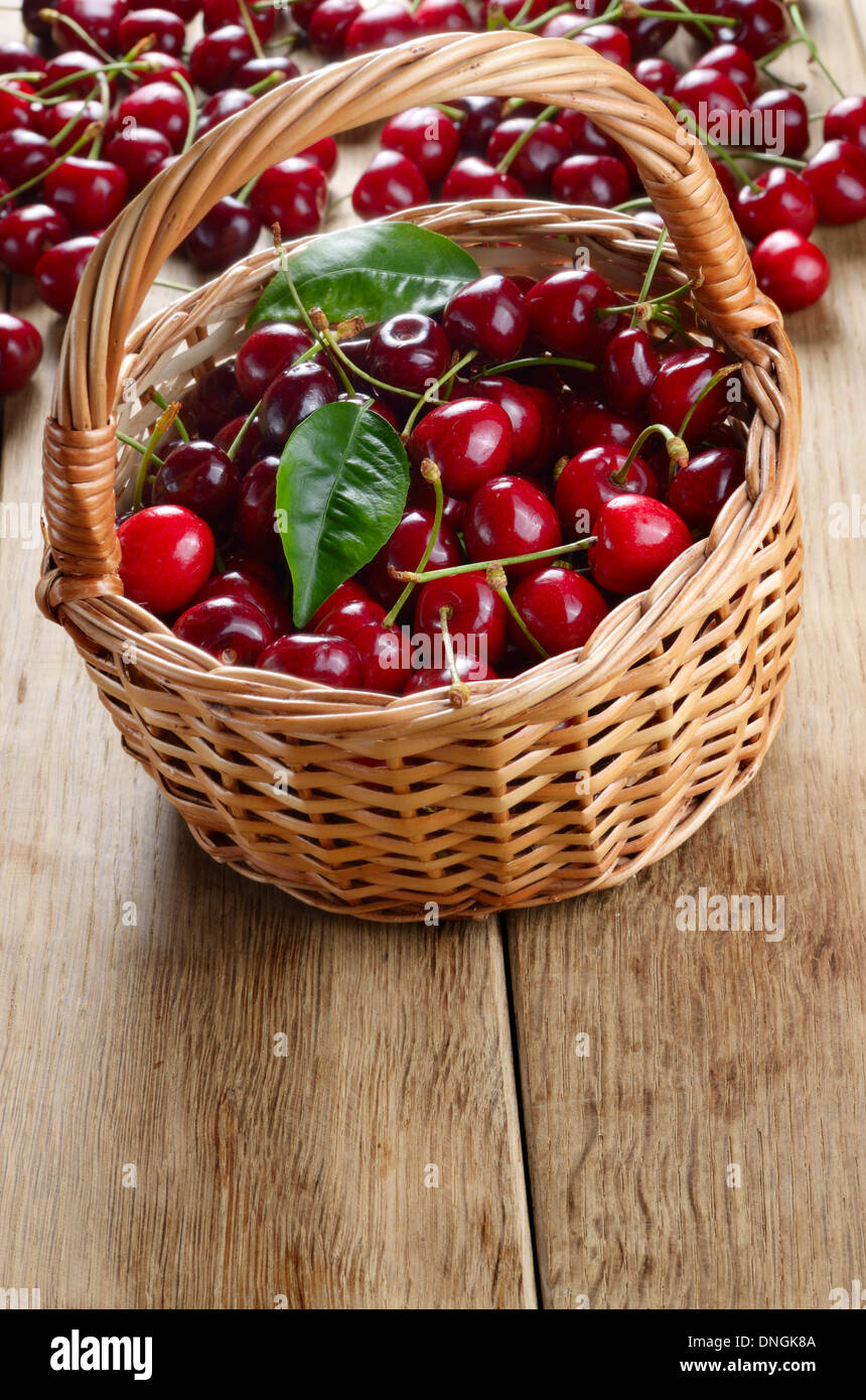 Basket of organic Cherries on wooden table - Stock Image