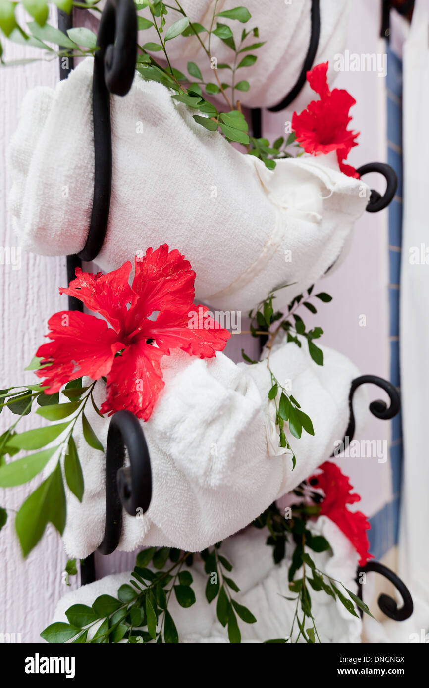 Towel Rack At The Spa With Fresh Hibiscus Flowers And Green Leaves