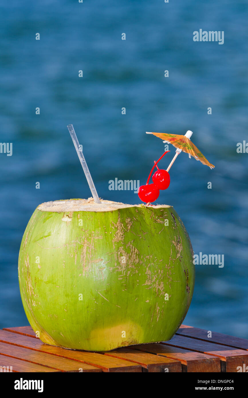 coconut drink served in a green coconut with rum and juices served on the beach of Belize - Stock Image