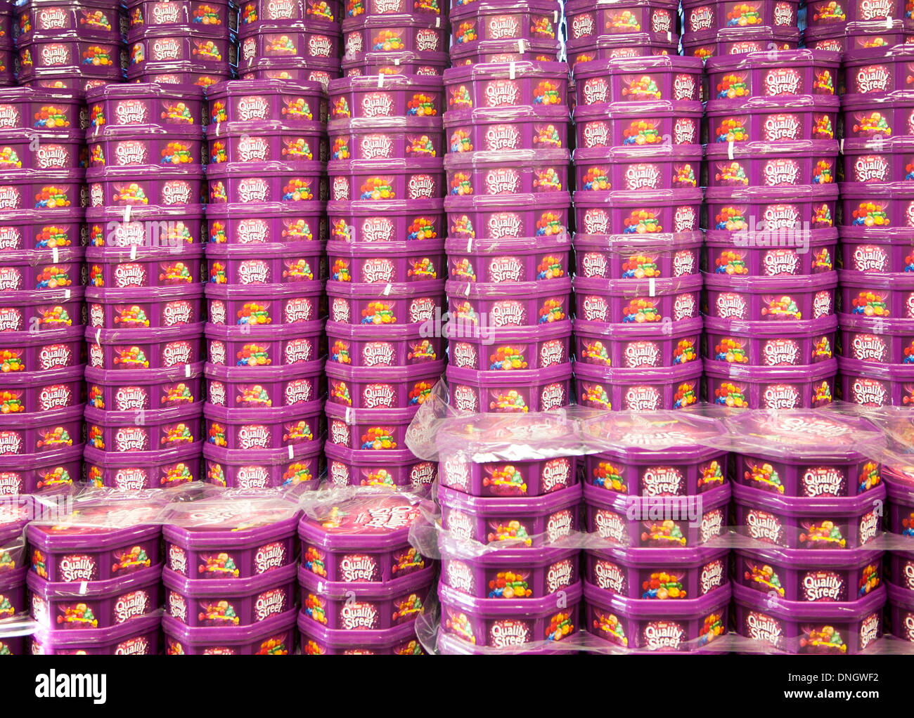 Piles of Quality Street chocolate tins piled up in a supermarket, UK - Stock Image