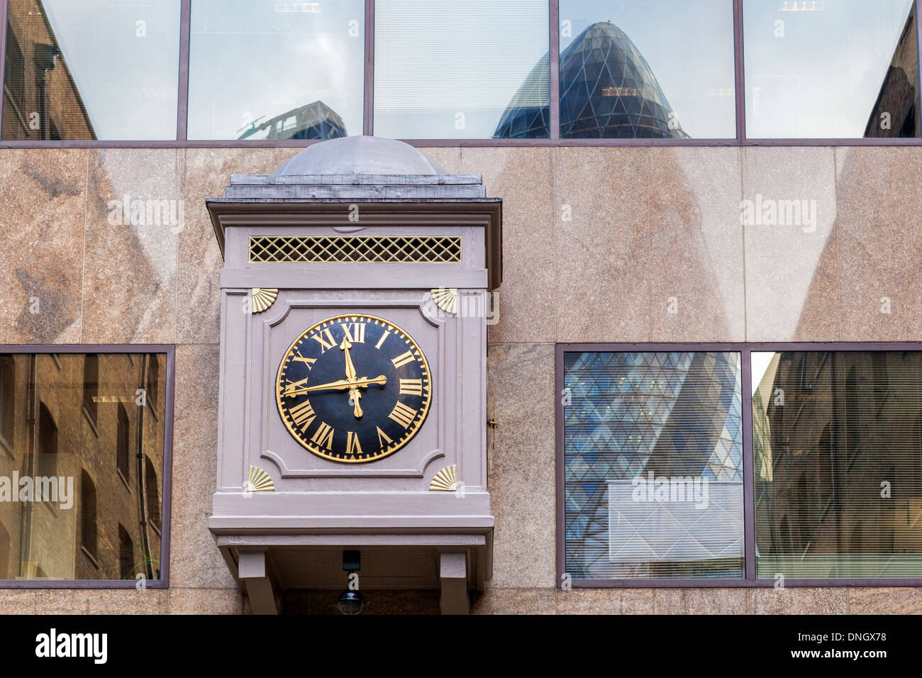 Clock with gold Roman numerals and reflection of 'The Gherkin' in a window at Devonshire Square, Spitalfields, London - Stock Image
