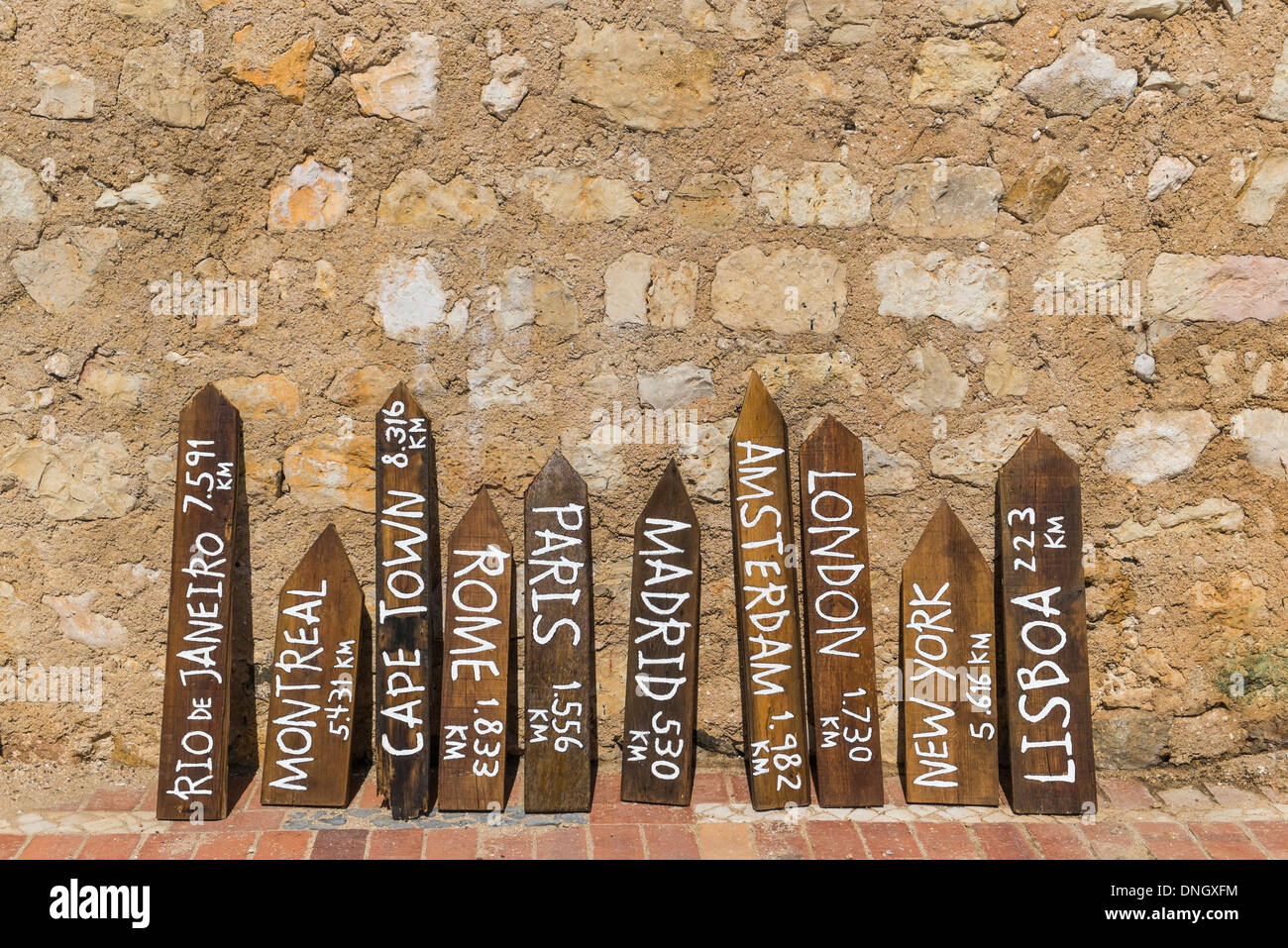 freshly painted distance indicators leaning on a natural stone wall, faro, algarve, portugal - Stock Image