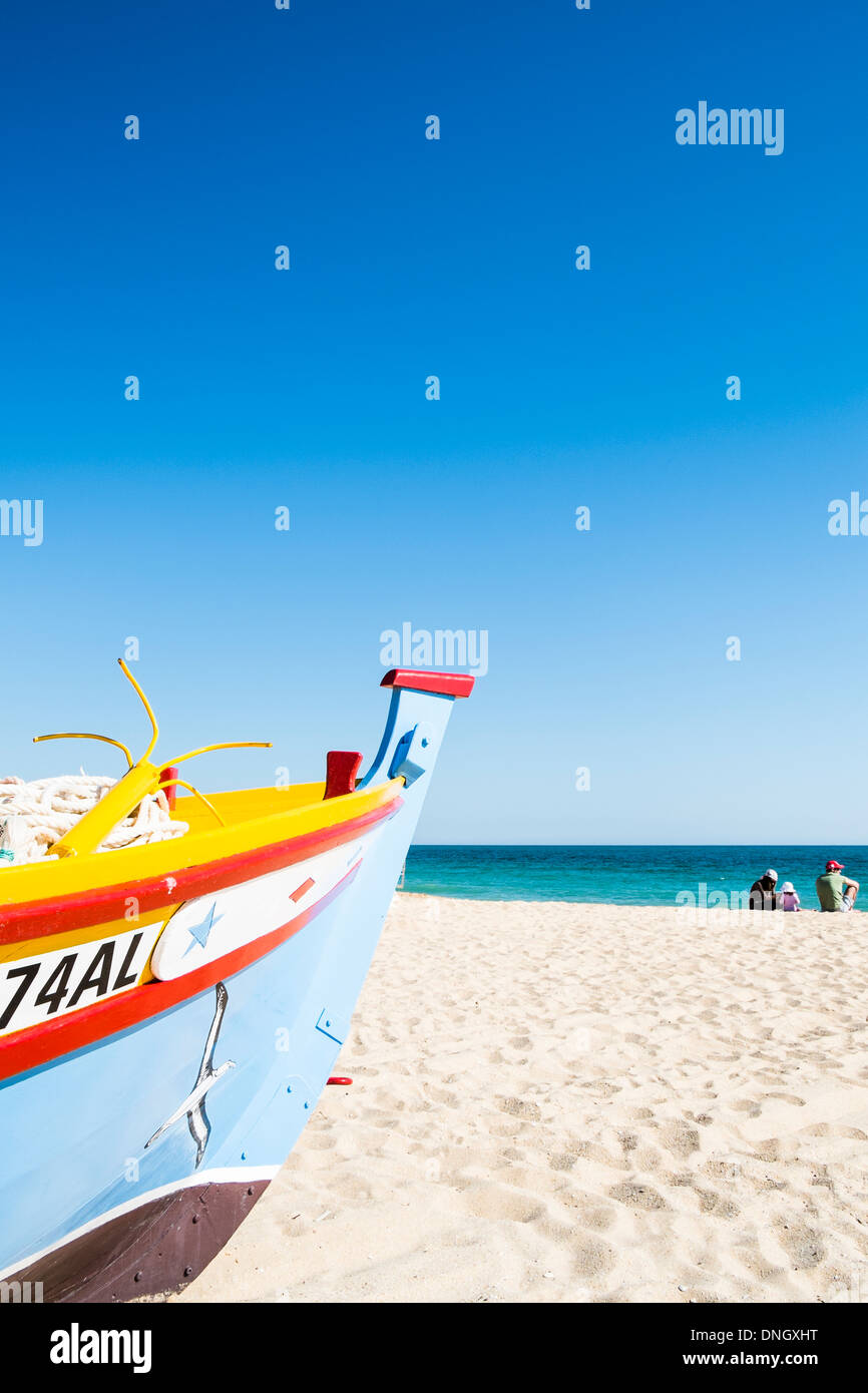 family sitting next to a traditionally painted fishing boat on the beach of armacao de pera , algarve, portugal - Stock Image