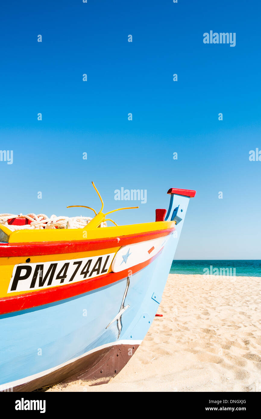 traditionally painted fishing boat on the beach of armacao de pera , algarve, portugal - Stock Image