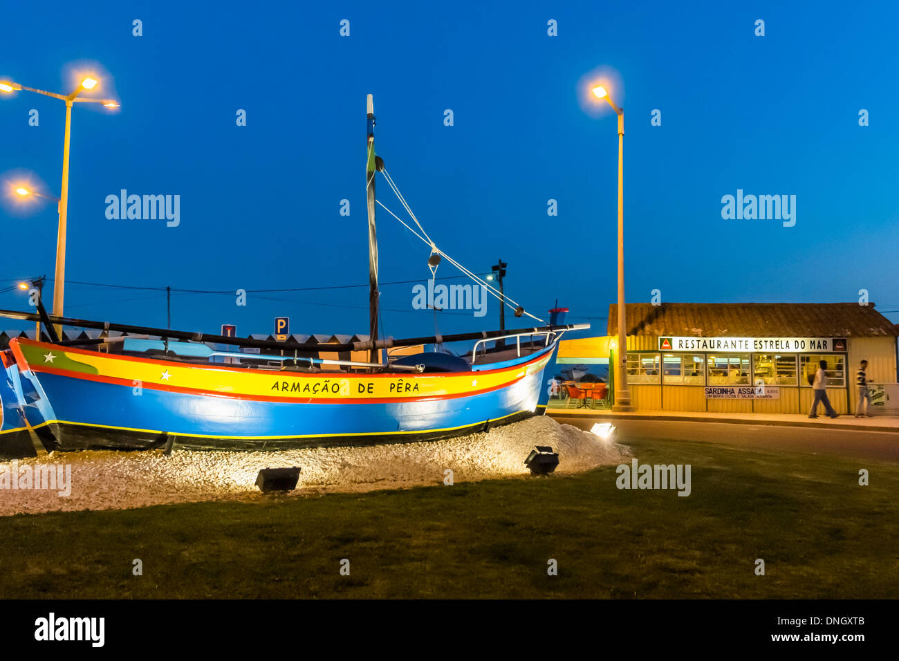 traditionally painted fishing boat in a roundabout traffic in front of restaurant _estrela do mar_ at night, armacao de pera, al - Stock Image