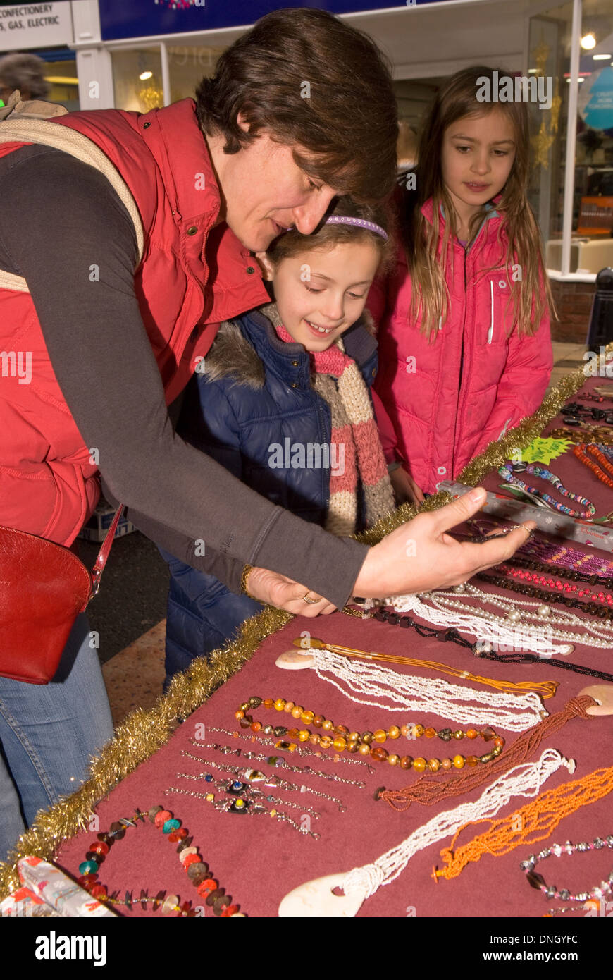 Mother with her 2 daughters (7 & 9 years) perusing jewellery stall at an annual christmas fayre, Petersfield, Hampshire, UK. - Stock Image