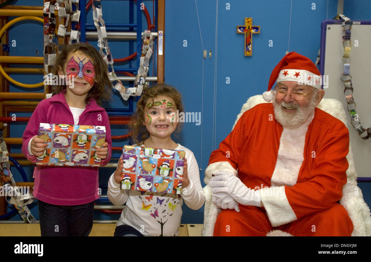 Happy looking youngsters having received presents from Father Christmas at a christmas fayre - Stock Image