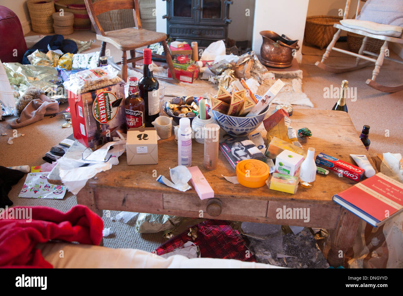 Mess of Christmas presents and wrapping paper scattered around a home, UK - Stock Image