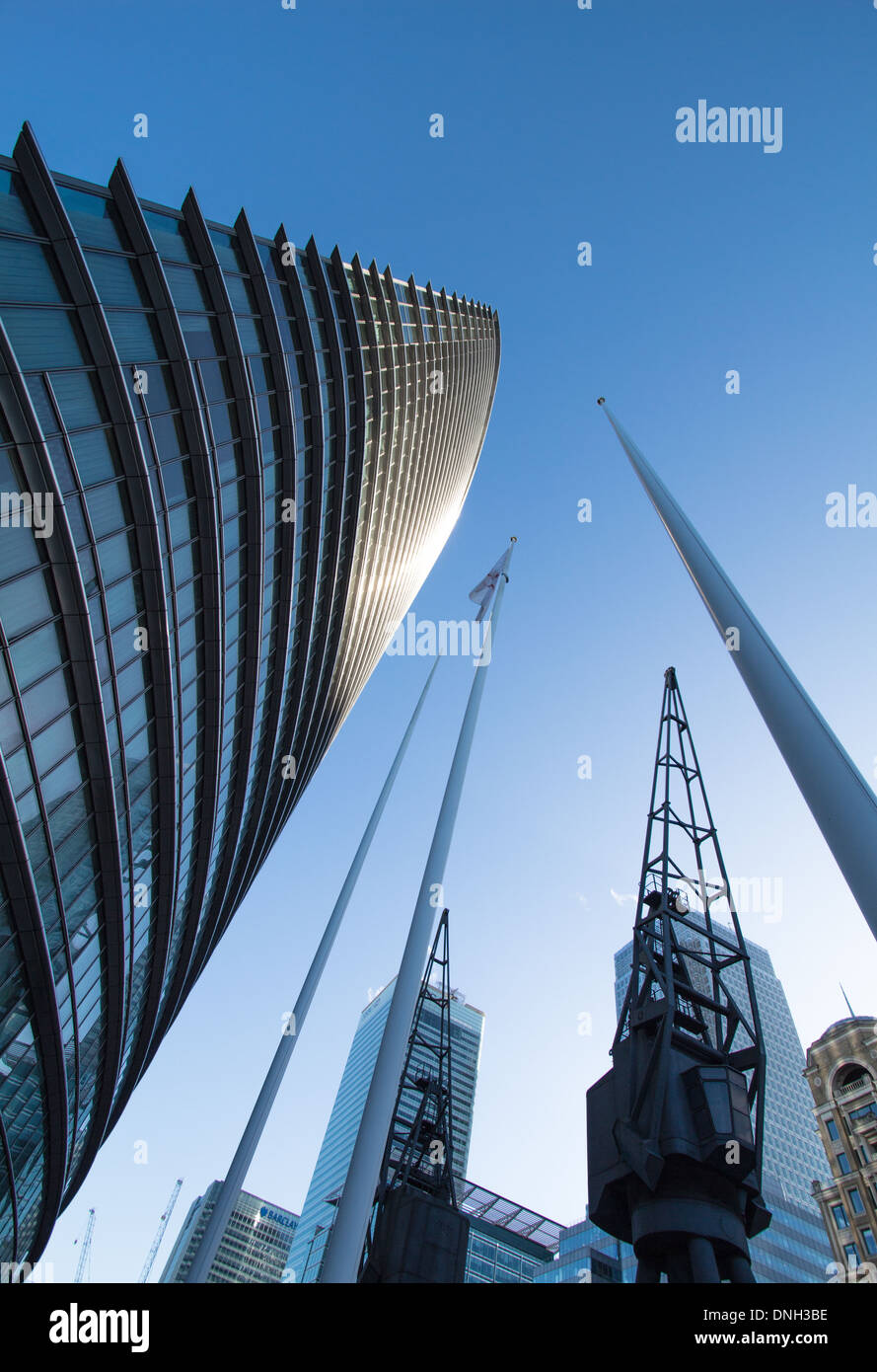 The Marriott Hotel Canary Wharf London Looking upwards next to flagpoles and docklands cranes - Stock Image