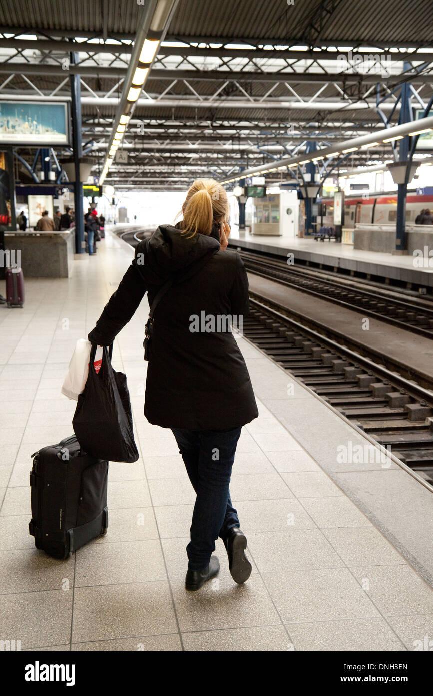 Woman rail traveller on station platform using mobile phone, Bruxelles Midi Railway station, Brussels, Belgium Europe - Stock Image