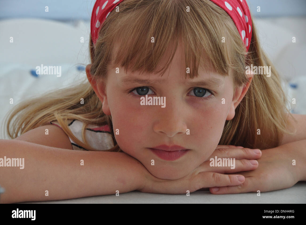 portrait of little blonde girl looking serious and sad looking directly into camera - Stock Image
