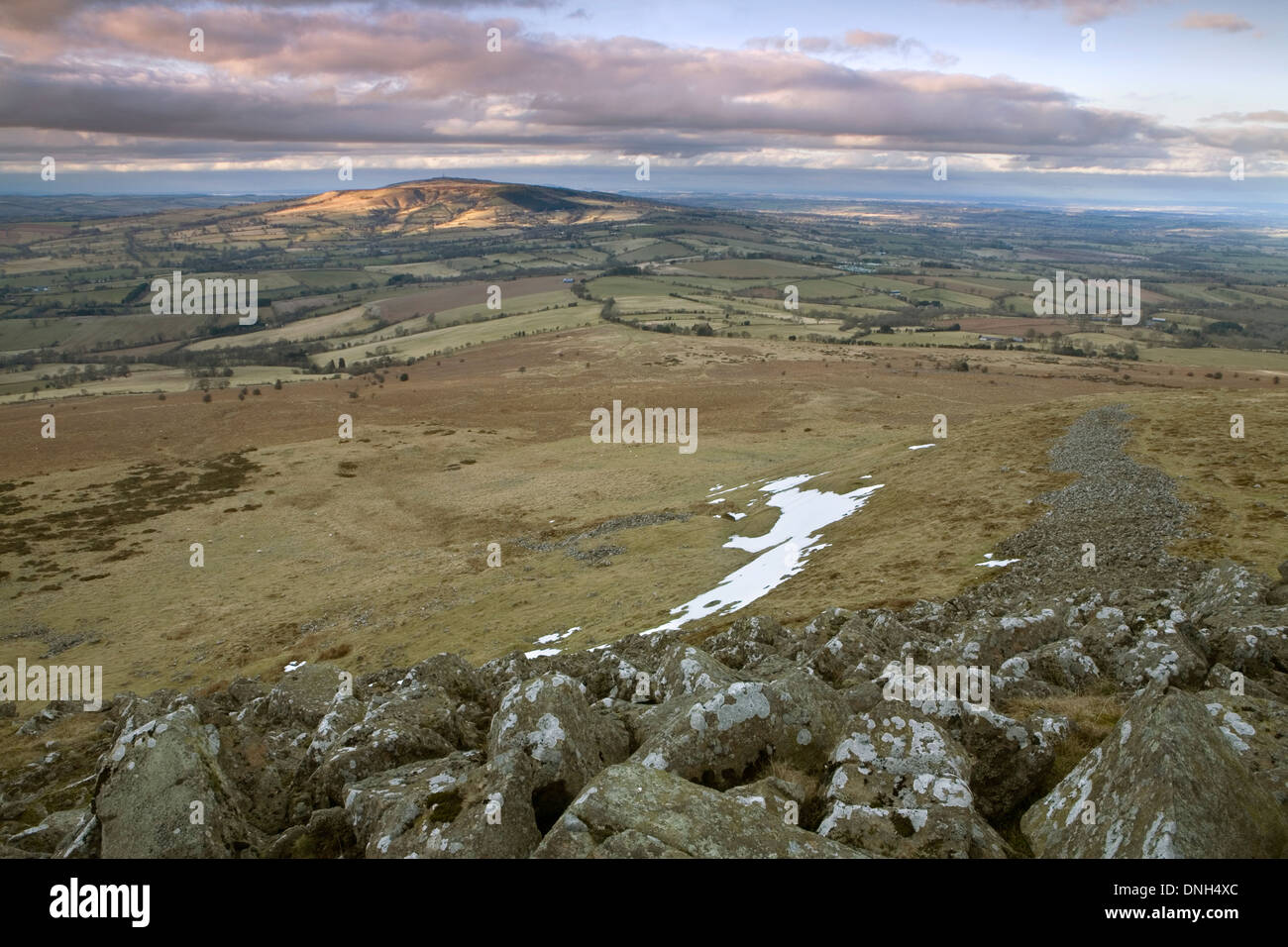 Brown Clee Hill being bathed in the last light of sunset on a cold Spring day in March. A few patches of snow remain Stock Photo