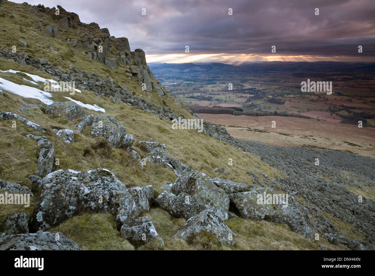 Lichen covered rocks on Clee Hill while the sun shines through the clouds creating Crepuscular rays in the background. Stock Photo