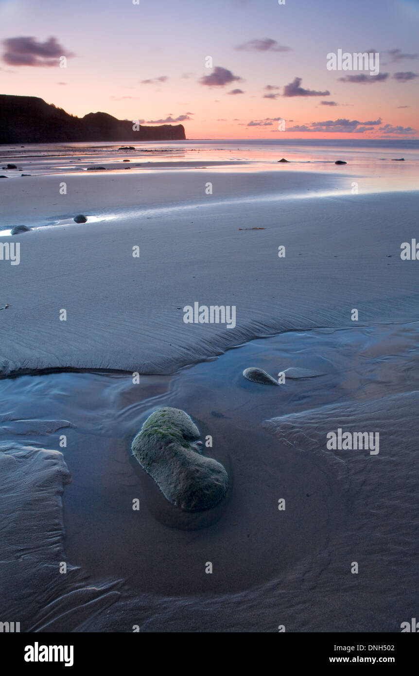 The retreating tide leaves a pool around a pebble in the sand on the beach at Sandsend, North Yorkshire at sunset. Stock Photo