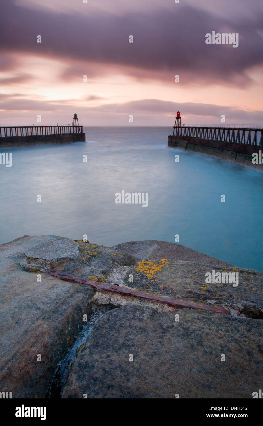 The breakwaters protrude directly Northwards into the North Sea each side of the mouth of the river Esk at Whitby, Stock Photo