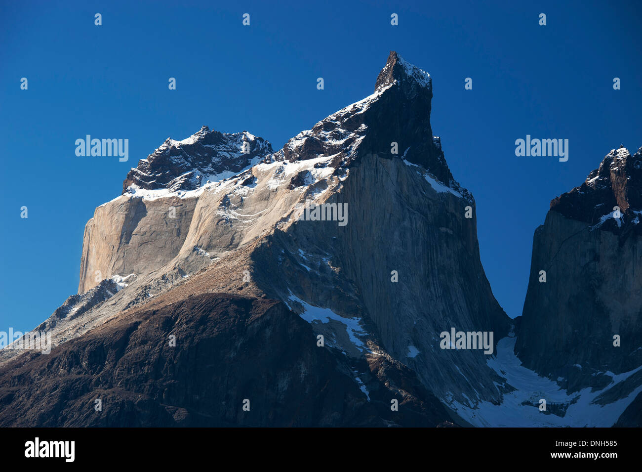 Sun-lit granite cliff in Torres del Paine national park - Stock Image