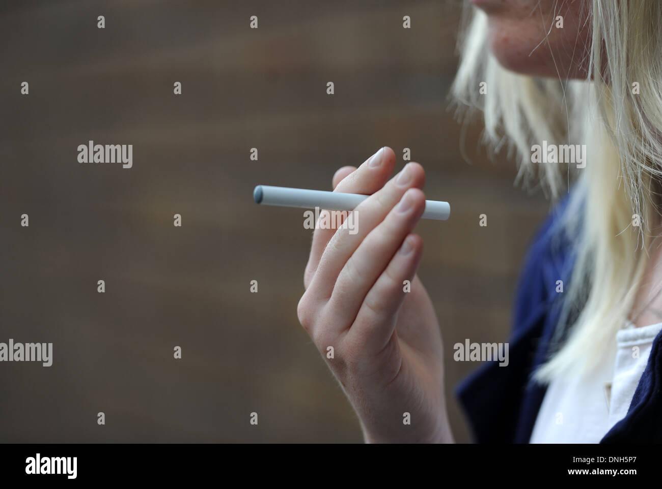 A female smoker holds an e-cigarette. - Stock Image