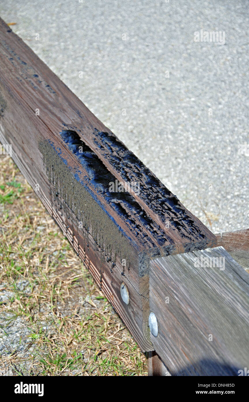 tar seeping out of a pressure treated beam in a road side guard rail - Stock Image