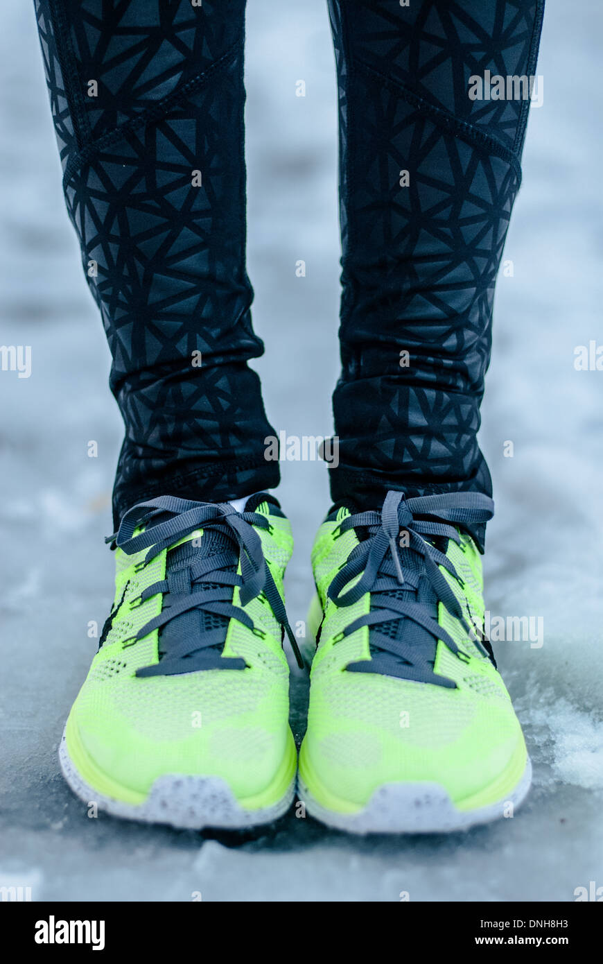 Closeup of a fit female runner's feet, in neon yellow running shoes, as she stands on an icy path on a cold winter day. - Stock Image